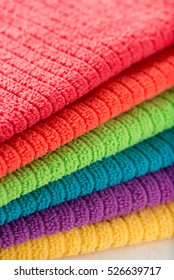 pile of bathroom towels in rainbow colors, isolated over a white background, close up, vertical