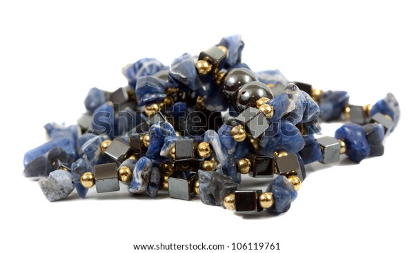 pile of beads of colored stones on white