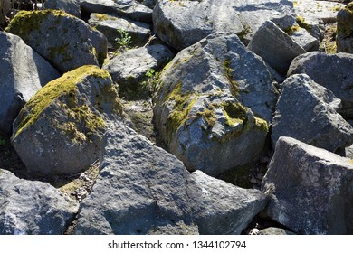 A pile of big grey rocks in a close up. Some of the rocks have some green moss growing from them. Photographed during a sunny summer day in Finland. Color image.