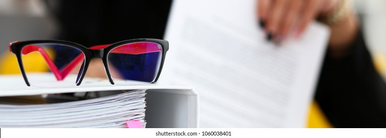 Pile of binder folders lying at worktable and stylish red black glasses closeup with female worker in background. Revision help internal revenue service agent investigation bank database workflow