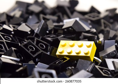 Pile of black color building blocks with selective focus and highlight on one particular yellow block using available light