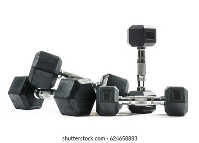 Pile of black dumbbell training weights isolated on white background. Weight training equipment.