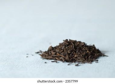 Pile of black Earl Gray tea on blue cloth