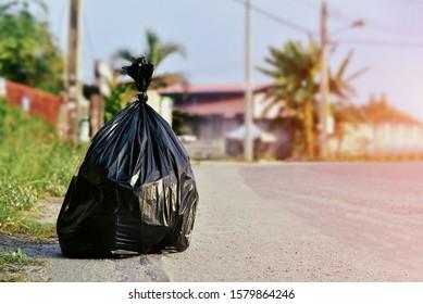 Pile of black garbage bag on footpath at side rode in city pollution trash