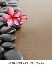 Pile of black stones with frangipani on wooden board