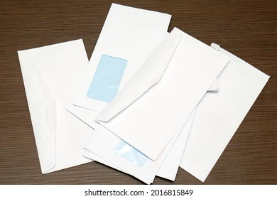 Pile of blank white paper envelopes on wooden table