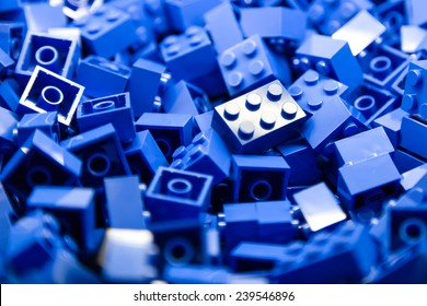 Pile of blue color building blocks with selective focus and highlight on one particular block using available light.