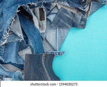 Pile of blue jeans scraps on a blue background. Top view with room for text.