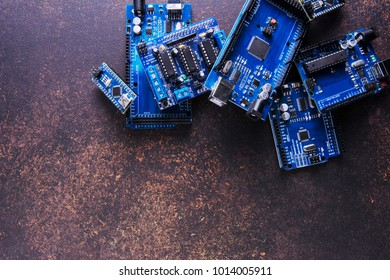 A pile of boards for prototyping and electronic research in a fablab or school on a rusty background.