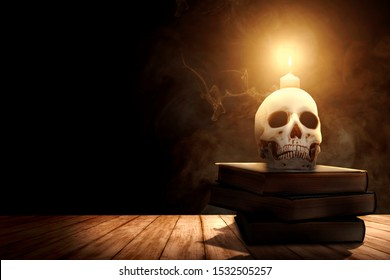Pile of the book with a human skull and candlelight on a wooden table over dark background