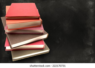 Pile of books in front of blackboard