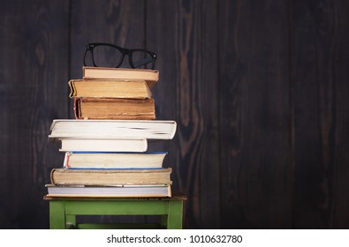 Pile of books and glasses from the top, a studio shot in retro style.