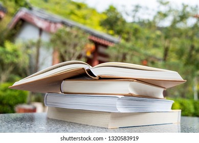 a pile of books on a garden stone table