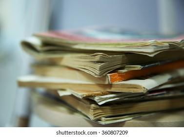 Pile of books on lamp shelf, close up
