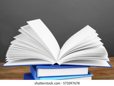 Pile of books on wooden table and grey background