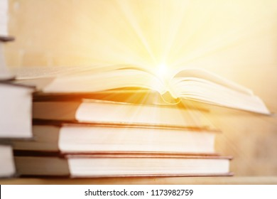 Pile of books with open book with rays of light. The concept of knowledge and enlightenment. Bookshelf with piled books.