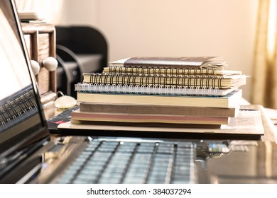 Pile of books and paperwork with blurred laptop, selective focus, shallow depth of field, vintage tone