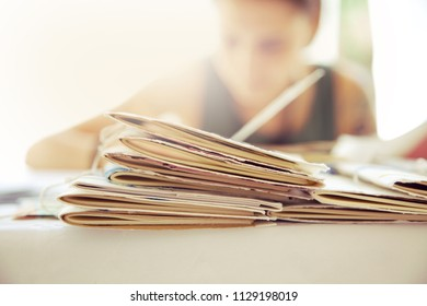 Pile of exercixìse books, a student on background