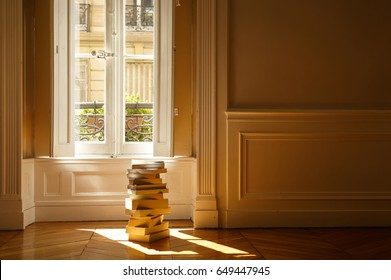 Pile of books in the sunlight in front of a window of a French apartment.