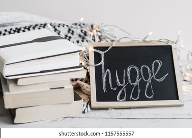 "Pile of books, warm knitted blanket, lights for home decoration and blackboard with text ""hygge"". Hygge concept"