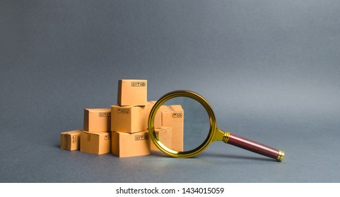 A pile of boxes and a magnifying glass. Concept search for goods and services. Tracking parcels. Quality control. Services for searching, comparing products from different trading companies.