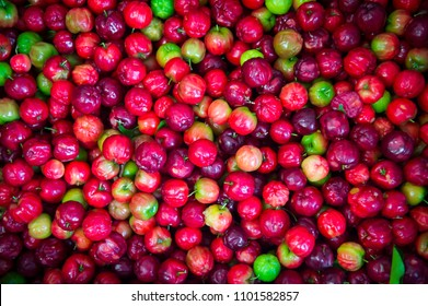 Pile of bright red acerola cherries stacked on display at an outdoor fruit and vegetable market in Salvador, Brazil