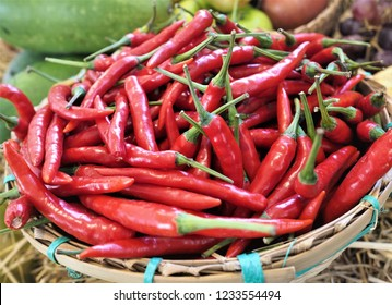 A pile of bright red Thai Chili peppers with green stem in the bamboo basket for sale in the spice market for making hot and spicy ingredients such as sauce or curry paste for Asian food and cuisine.