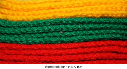 A pile of bright yellow, green and red knitted elements. Warm and soft background, wallpaper, pattern. Lithuanian flag