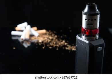 Pile of broken cigarettes with modern electronic cigarette