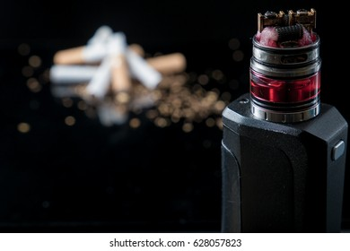 Pile of broken cigarettes with modern electronic cigarette with opened tank