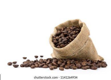 Pile of brown roasted coffee beans  in sack bag spill on white background,fresh and bright wallpaper concept.