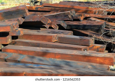 A pile of brown wooden railway sleepers outdoor on an autumn day