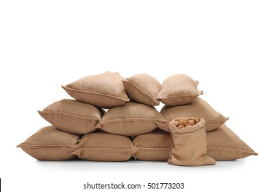 Pile of burlap sacks filled with potatoes isolated on white background