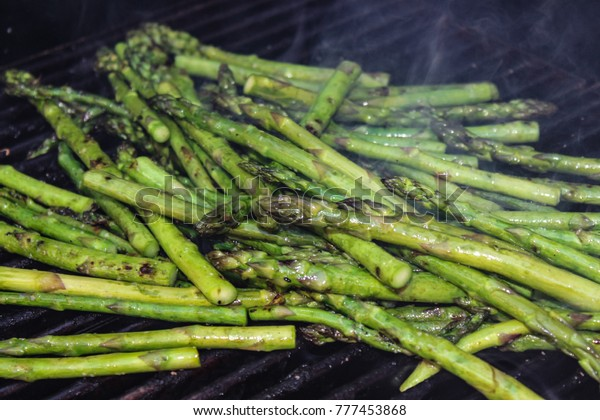 A pile of buttered asparagus spears roasting  on an outdoor grill with smoke coming off of them