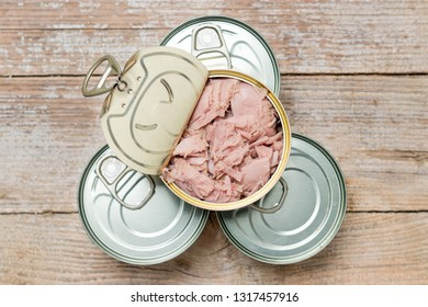 Pile of canned tuna in top view. Healthy conversed sea food on a wooden table.