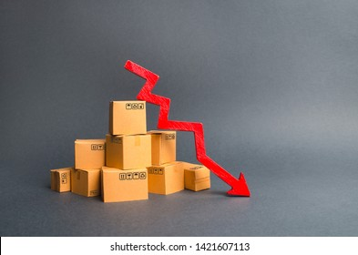 A pile of cardboard boxes and a red arrow down. The decline in the production of goods and products, the economic downturn and recession. Falling consumer demand, declining exports or imports.