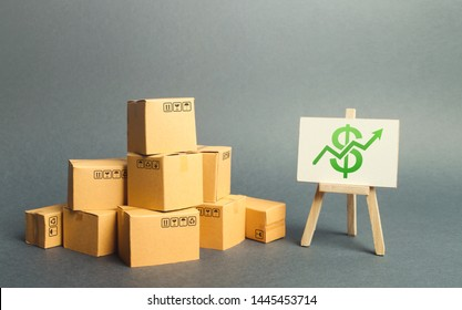 A pile of cardboard boxes and a stand with green arrow up. Increasing consumer demand. rate growth of production of goods, increasing economic indicators. Trade balance. value added products