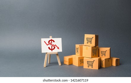 A pile of cardboard boxes and stand with a red down arrow. decline in the production of goods and products, the economic downturn and recession. Falling consumer demand, Falling prices, lower profits