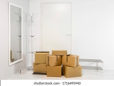 Pile of cardboard boxes in white minimalist white home hallway. Lot of room for text.