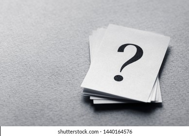 Pile of cards with printed question marks on a textured grey surface with copy space in a conceptual image