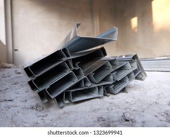 A pile of ceiling rail track on the floor of a house under consruction.