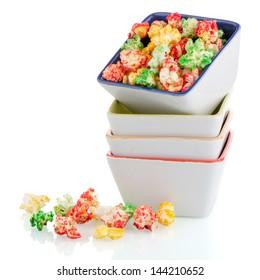 Pile of ceramic bowls of popcorn on white reflective background.