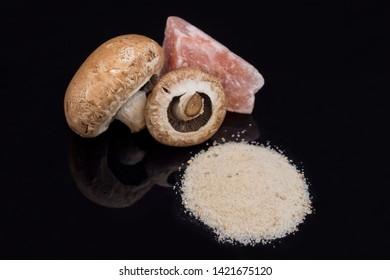 A pile of champignon salt with mushrooms and a stone of Himalayan salt