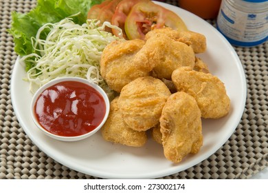 A pile of chicken nuggets on white plate with sauce