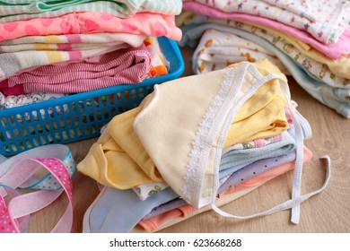 A pile of children's clothes. Many clothes for children are stacked on the table. A stack of colorful clothes for babies. Romper suit and baby's loose jacket in the basket for things.