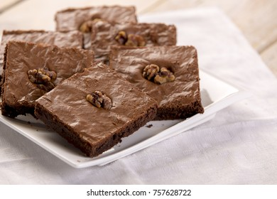 Pile Of Chocolate Brownies Whit Walnuts On A White Plate With Wooden Table  And Light Coloured