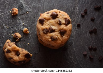 Pile of Chocolate Chip Cookies with Crumbs and Chips on a Dark Surface viewed from the top