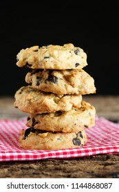 Pile of chocolate chip cookies on napkin with dark background.