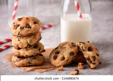 Pile of Chocolate chip Cookies on a Mable surface with a bottle of milk