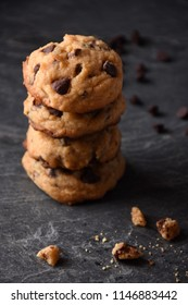 Pile of Chocolate Chip Cookies on a Dark Background with Crumbs